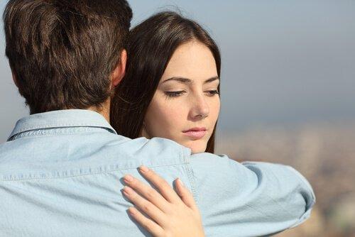 Chica-triste-mirando-hacia-un-lado-mientras-abraza-a-su-novio